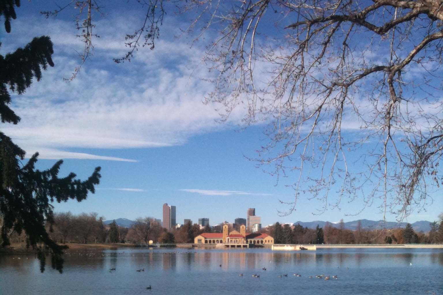 A view of the lake and skyline in Denver's City Park.
